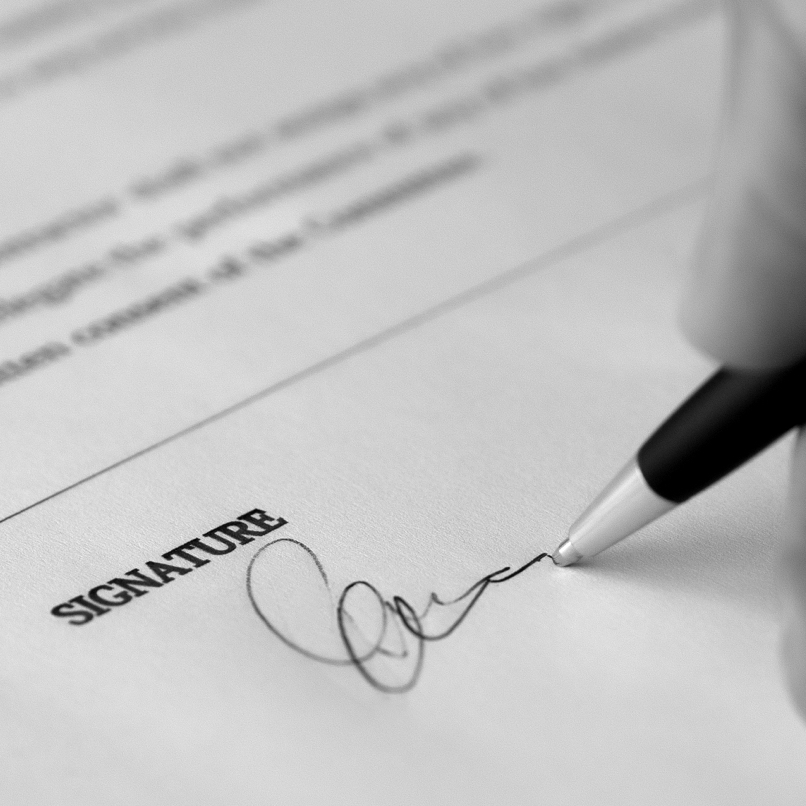 Close-in view of a pen in the process of signing a contract.