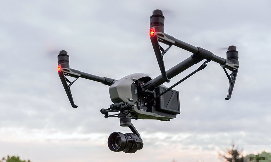 A drone carrying a camera flies through the sky, capturing overhead footage of a Tri-North Builders construction site.