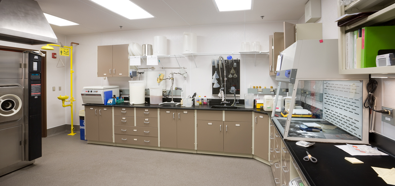 A loboratory in the Danisco building features a bench with a sink, emergency eye wash station, a fume hood and more.