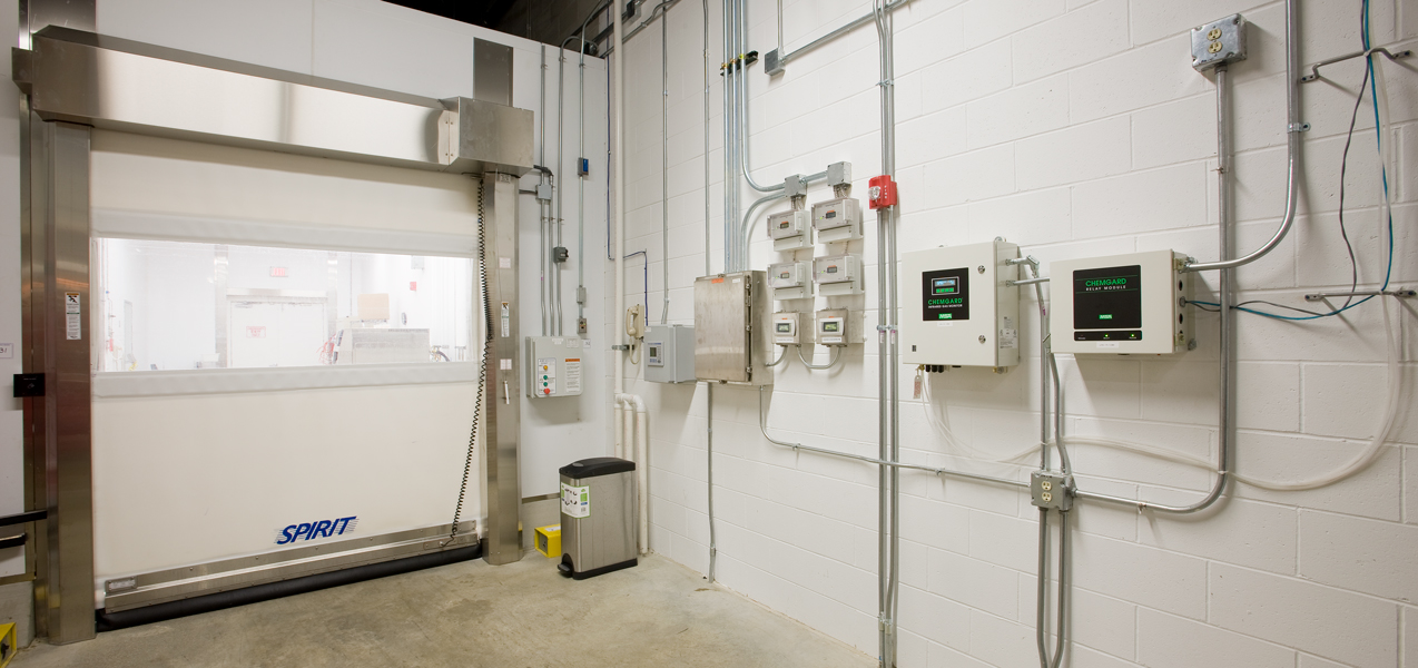 An interior garage door and a wall with several control panels installed.