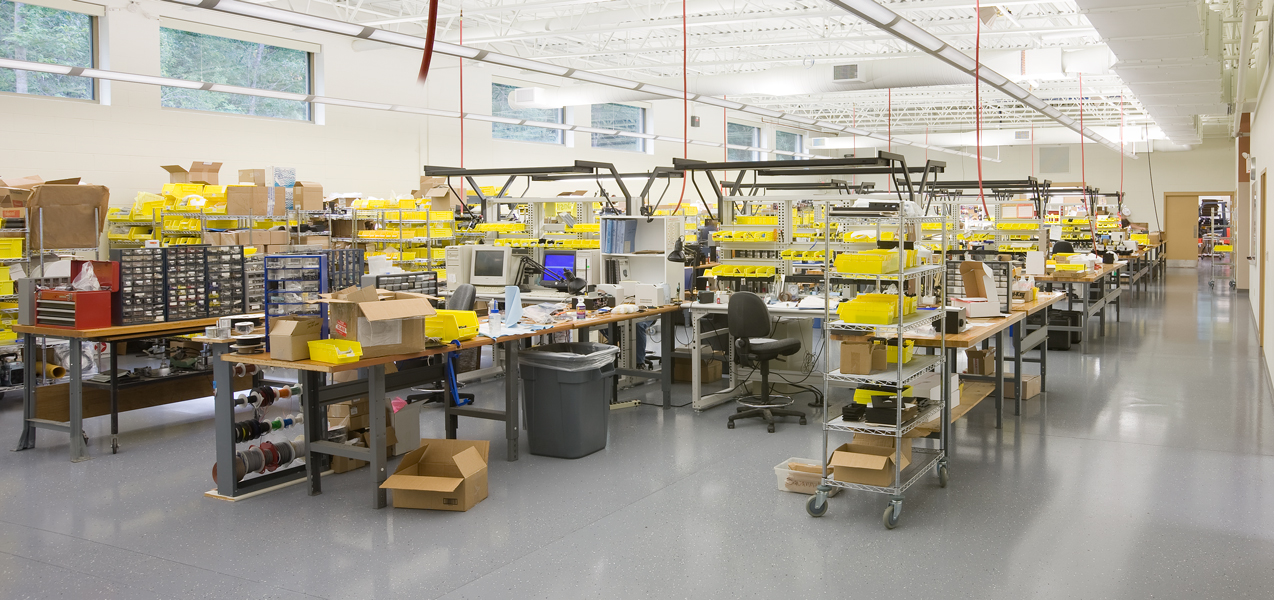 Desks, tables and carts of supplies fill the assembly room at PIKE Technologies in Fitchburg, WI.